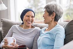 Mulher em tratamento contra o câncer conversando com outra mulher