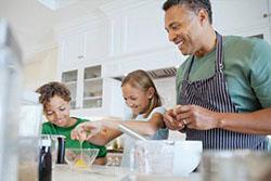 Homem cozinhando com crianças