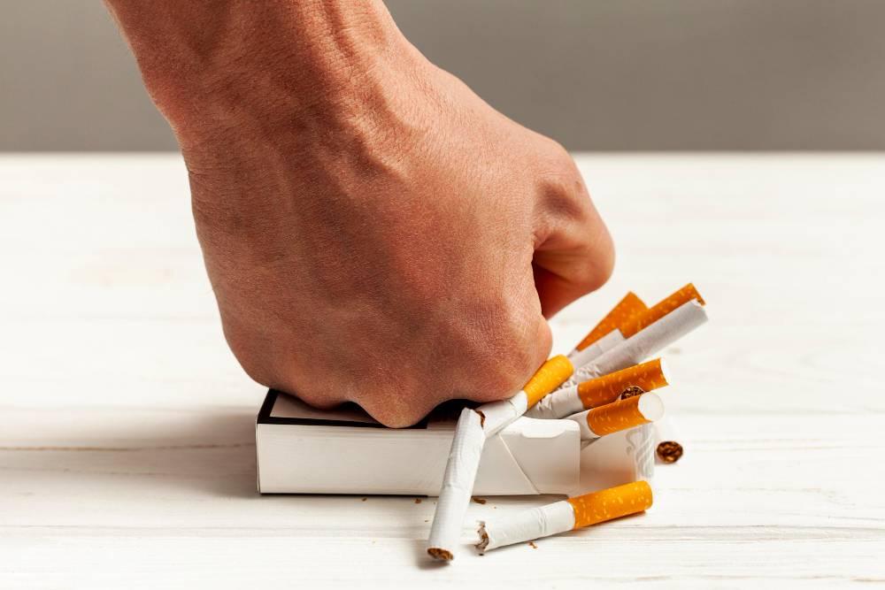 Ex-fumante esmagando maço de cigarros