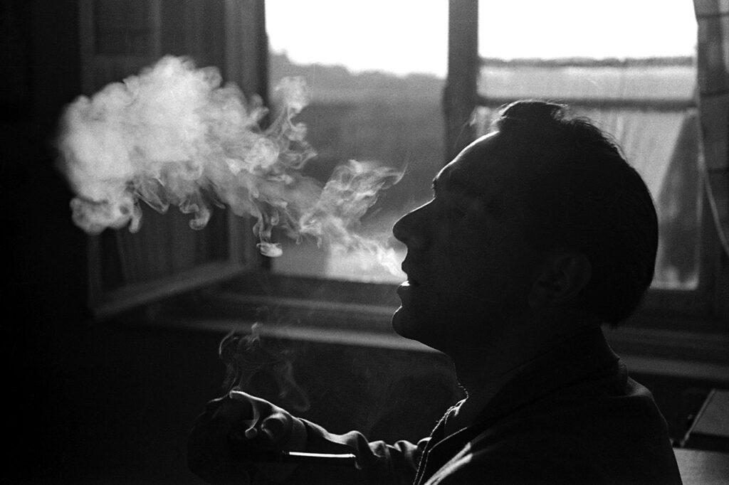 homem fumando na janela